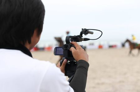 Man holding camcorder as working recording on a beach Polo Tournament sport Stock Photo