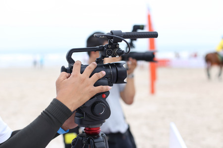 outdoor event: Man holding camcorder and camera working on recording a beach Polo Tournament sport