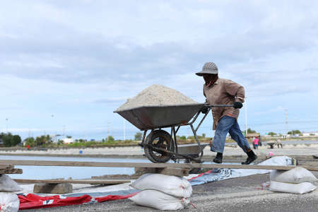 unprocessed: Unidentified people pushing trolley full of unprocessed salt in salt pan in Thailand Stock Photo