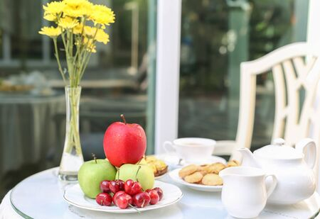 yellow tea pot: Tea time with chocolate and cookies or biscuit and fruit in the garden Stock Photo
