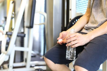 sportingly: Man silling down holding bottle water having a break after workout in gym