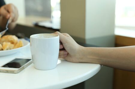 cappaccino: Woman hands with latte coffee and cellphone on a white  table Stock Photo