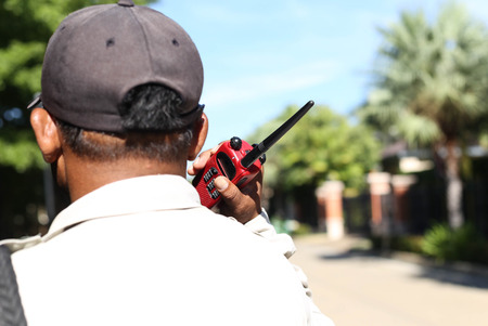 Security guard hand holding cb and talking on walkie-talkie radio