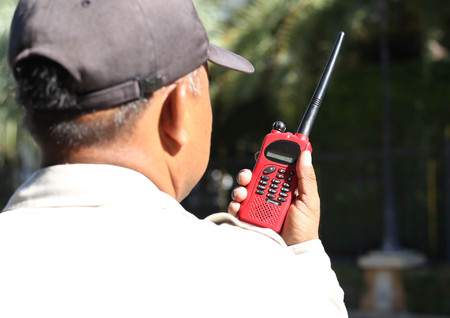 cb: Security guard hand holding cb and talking on walkie-talkie radio