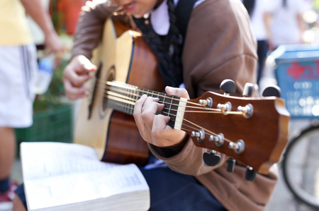 blonde teenage girl: Teenage school girl playing an acoustic guitar with guitar song book Stock Photo
