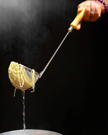 Cooking egg or yellow noodle in hot water isolated in black background