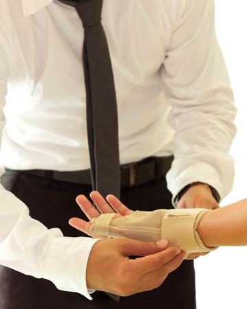 Doctor bandaging female broken hand in white background