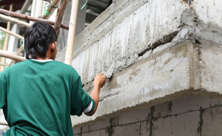 Asian boy hand using trowel with wet concrete wall in Thailand