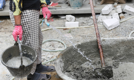 constrution site: Constrution work put water on concrete mixing tray in building site Stock Photo
