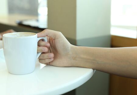 gaffe: Woman hands with latte coffee on a white  table Stock Photo
