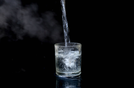 Pouring hot water into glass isolated on black background