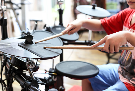 Unidentified Asian boy play electronic drum in music room Standard-Bild