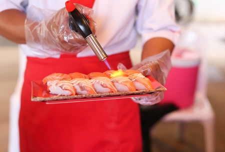 Japanese restaurant chef grilling salmon sushi with a torch burn