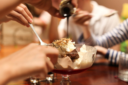 postres: Familia que disfruta de d�a sin tener una crema de helado en un restaurante Foto de archivo