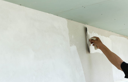 Plasterer spreading plaster to wall with trowel