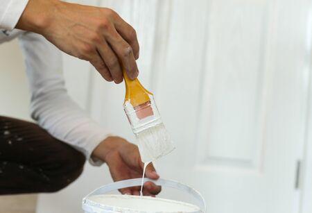 pintor: Pintor de la mano sosteniendo el pincel de color amarillo para decorar