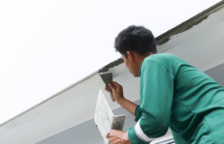 Unidentified man plastering  concrete to shape the edge of the wall on house construction of the wall on house construction Standard-Bild