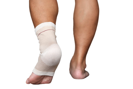 ankle strap: Man injured ankle and foot wrapped in bandage in white background Stock Photo