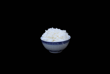 Bowl of boiled rice isolated in black background Stock Photo
