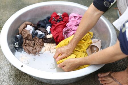 wench: Hands wash stain of dirty clothes in big bowl