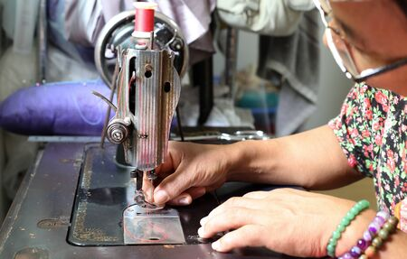 threading: Woman hand threading needle into sewing machine needle for clothes making Stock Photo