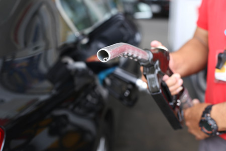 fcc: Man holding petrol pump nozzle in gas station