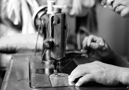 threading: Woman hand threading needle into sewing machine needle in black and white