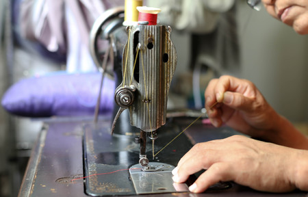 Woman hand threading needle into sewing machine needle for clothes making Stock Photo