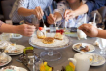 fiesta familiar: concepto borroso de amigos maduros que tienen pedazo de pastel en la mesa