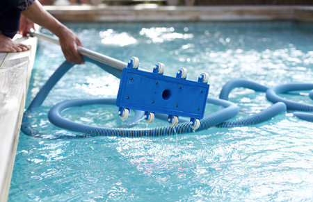 Man holding an equipment for cleaning the ground of the swimming pool