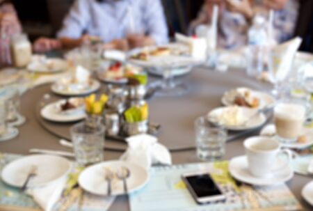 left behind: Blurry group of people after having food and cake leftover on the table Stock Photo