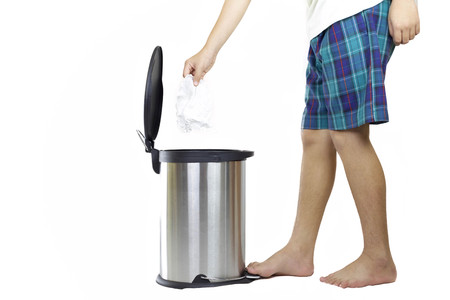 School boy keep clean environment by put tissue paper in rubbish bin