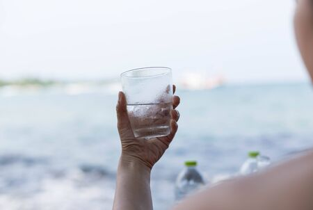 clod: Woman hand holding  glass with clod drink by the beach