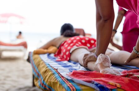 Woman having foot scrub and massage on the beach