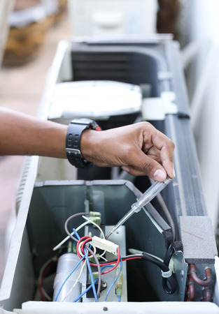 test probe: Electrician hand holding a detector with multimeter probe on air compressor