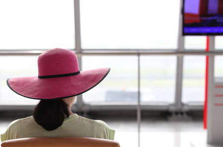 viewport: Woman with a pink hat waiting for a flight in the airport terminal with back viewport