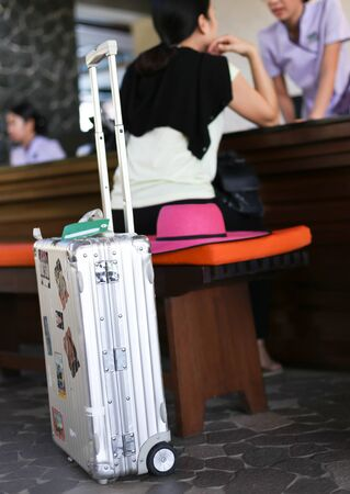people travelling: Woman with silver suitcase in checking in at hotel the reception Stock Photo