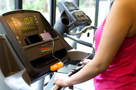 body parts cell phone: Woman exercise on the running machine at the gym and listen to cell phone