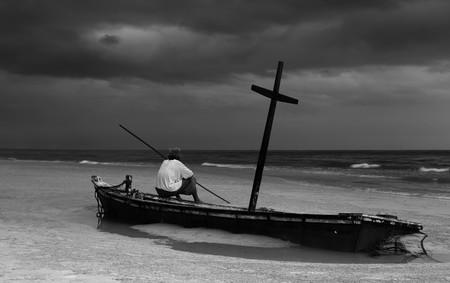 persona triste: Viejo hombre no identificado en el barco wereck en la playa con nube de tormenta en contraste Blanco y Negro Foto de archivo