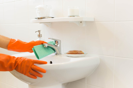 Woman cleaning water tap witn orange glove Archivio Fotografico