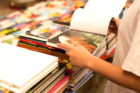 Asiática joven muchacho que lee un libro en una librería Foto de archivo - 50862734