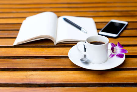 oncept: Cup of coffee with flower and note book  on the table and  cell phone