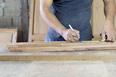 carpintero: madera de medición del carpintero macho en su taller con la pluma