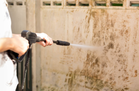 pressure washing: Woman cleaning dirty waill with high pressure water jet