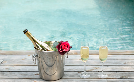 Champagne bottle in ice bucket with flower and champagne glass by swimming pool Archivio Fotografico