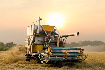 man machine: Unidentified man with Harvester machine to harvest rice field working in Thailand Stock Photo