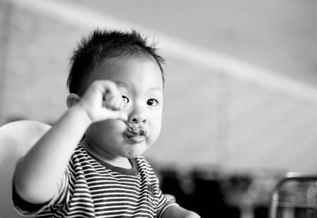 baby chair: At Bangkok Thailand  in March 5, 2016 : Baby looking aways while eating food  with spoon in baby chair