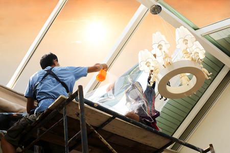 Enrubanneuse personnes non identifiées teinter une fenêtre de maison de verre avec une feuille teintée ou d'un film à l'aide du brouillard de pulvérisation