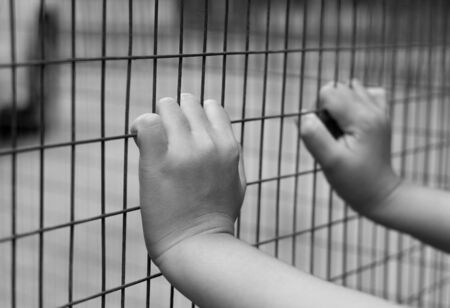 killer cells: Hand of prisoner grabbed the metal  fence in black and white Stock Photo