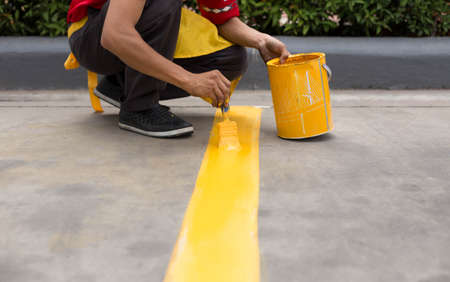 infra construction: Man painting the yellow line on the concrete floor at car park